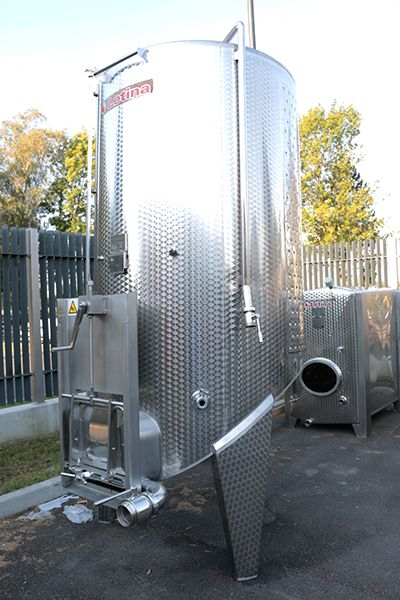 Side view of a jacketed 3300 L Letina VIKS used stainless steel pump-over fermenter with a spoon bottom and guillotine door for sale.
