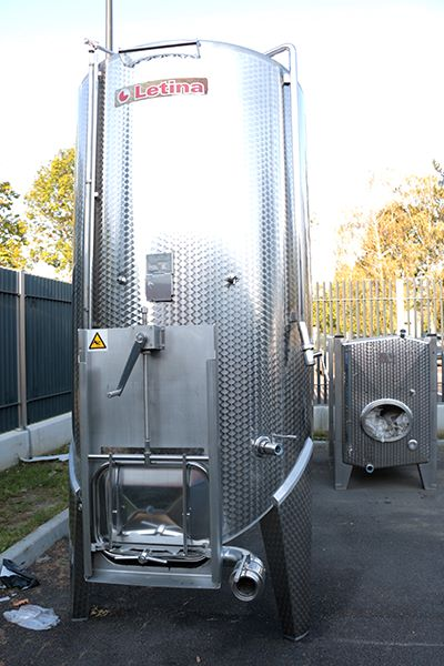 Front view of a 3300 L Letina VIKS used stainless steel pump-over fermenter with a spoon bottom and guillotine door for sale.