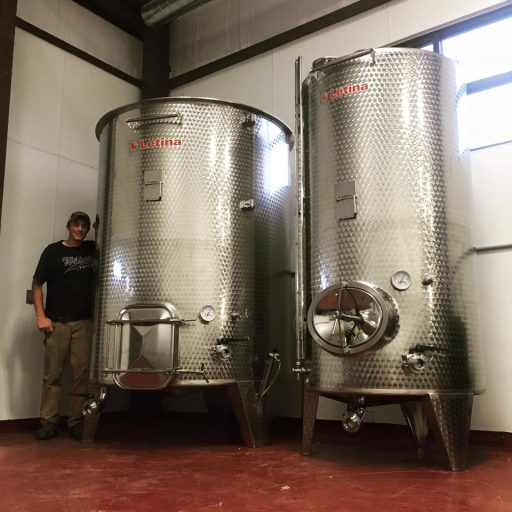 Man standing next to two stainless steel wine tanks in Liquid Art Winery in Kansas, USA.