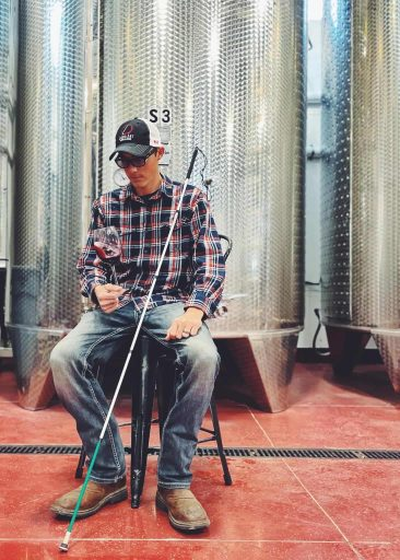 Man sitting in front of a wine tank in the Liquid Art Winery in Kansas, USA.