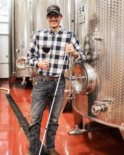 Man leaning on one of his Letina wine tanks in the Liquid Art Winery in Kansas, USA.