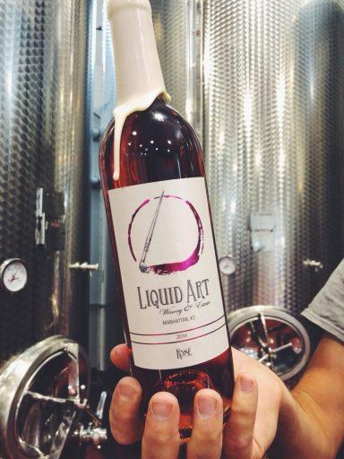 Bottle of wine in front of wine fermenters in Liquid Art Winery in Kansas, USA.