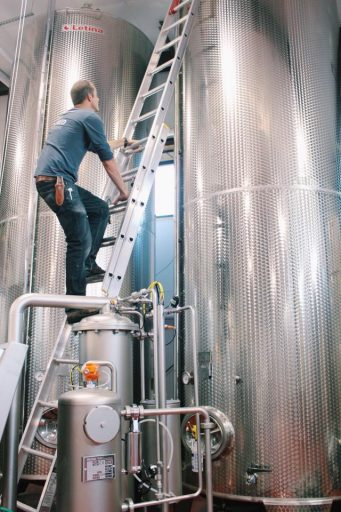 Man climbing a ladder on a large Letina stainless steel wine tanks in the Liquid Art Winery in Kansas, USA.