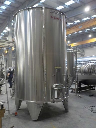 Side view of a professional, polished 9950 L stainless steel Letina PZPK sloped variable capacity tank for red wine with a cooling jacket.