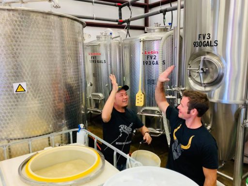 Men high-fiving in front of a Letina tank in Superstition Meadery in Arizona, USA.
