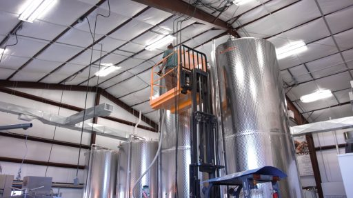 Man cleaning a tall Letina tank at Superstition Meadery in Arizona, USA.