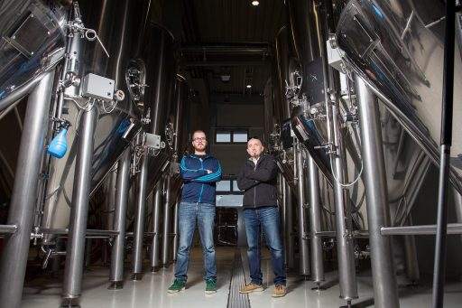 Men posing for a photo in front of the conical fermenters in the Varionica brewery in Croatia.